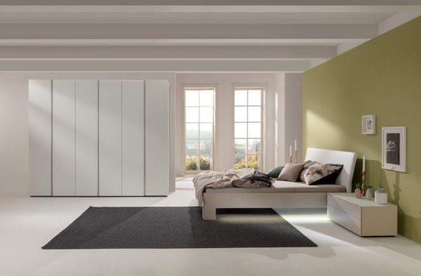 01: Schlafzimmer mit Drehtürenschrank in Glas und Bett mit Komforthöhe