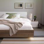 20: Bett mit Kufenuntergestell, kombiniert mit Nussbaumholz und gepolstertem Kopfteil in weiss. Mit sehr schönem Inlay in der Bettkante, ebenfalls in weiss