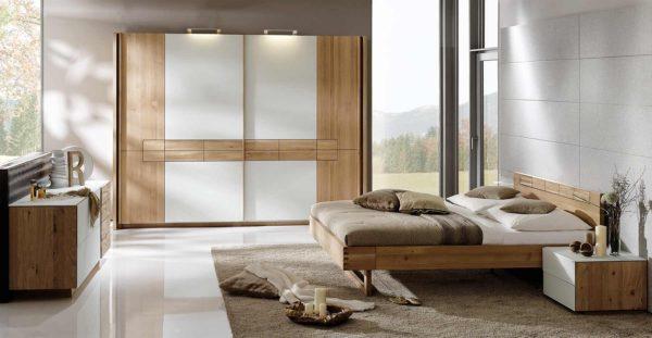06: Schlafzimmer in Massivholz. Schwebetürenschrank mit Glasfronten in weiss und geschroppten Akzenten in Holz